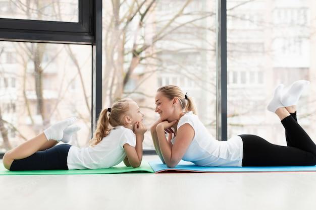 Vue Latérale De La Mère Et La Fille Posant Sur Un Tapis De Yoga Photo gratuit