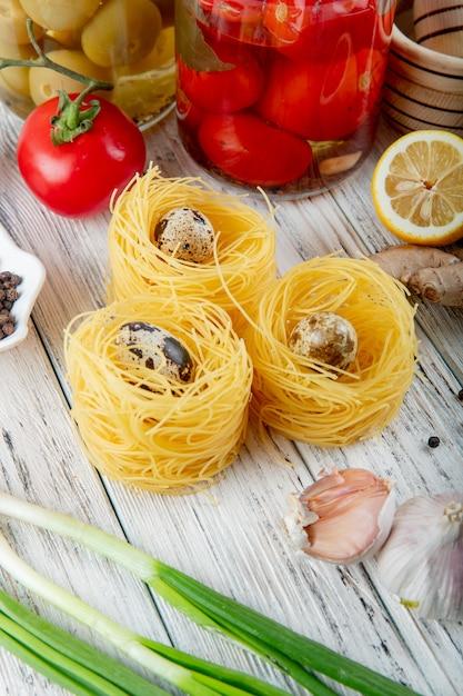 Vue Latérale Des œufs Entourés De Vermicelles à L'ail De L'oignon Vert De Tomate Et Citron Coupé Sur Fond De Bois Photo gratuit