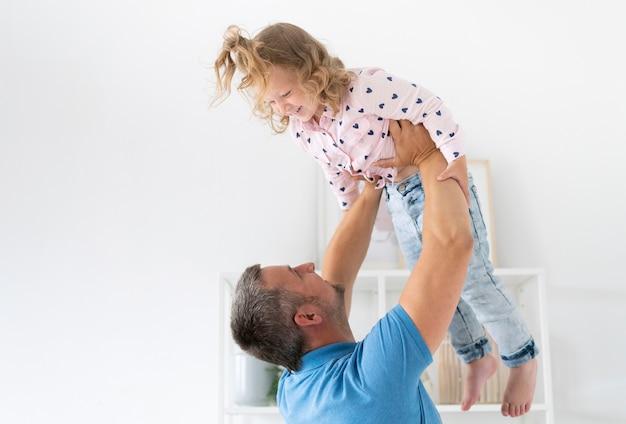 Vue latérale d'un parent tenant son enfant Photo gratuit