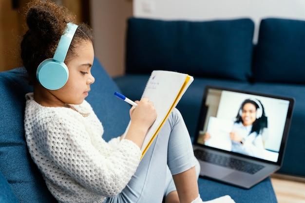 Vue Latérale De La Petite Fille Au Cours De L'école En Ligne Avec Ordinateur Portable Et écouteurs Photo gratuit
