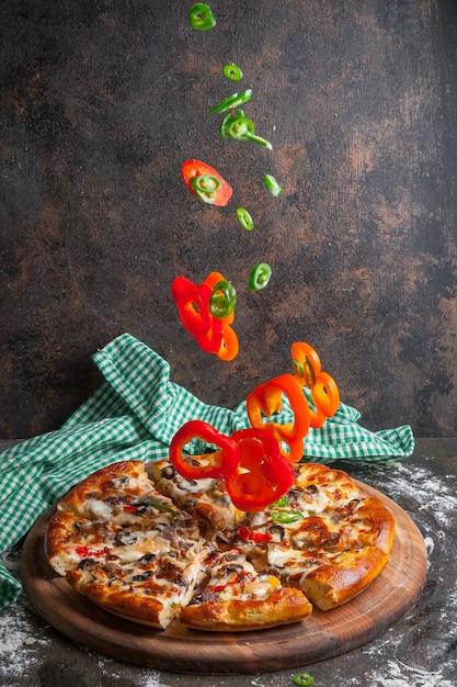 Vue Latérale Pizza Avec Des Tranches De Poivron Et Des Tranches De Pizza Dans Des Ustensiles De Cuisine à Bord Photo gratuit