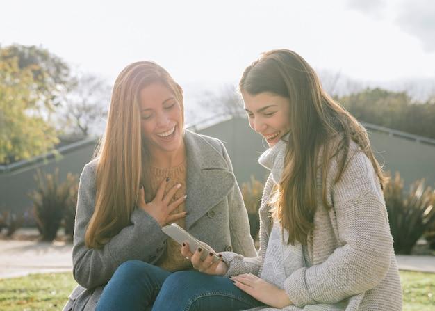 Vue latérale, plan moyen de deux jeunes femmes regardant le téléphone dans le parc Photo gratuit