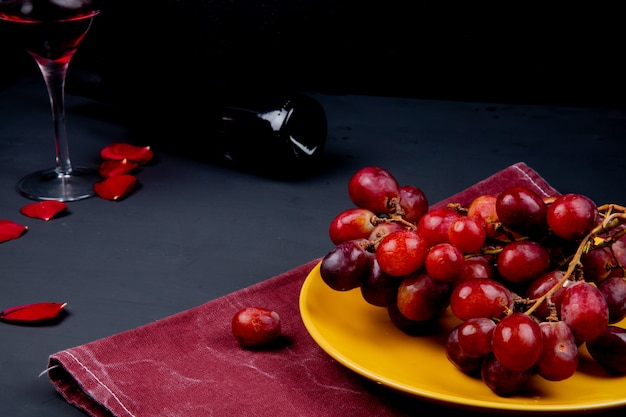 Vue Latérale De La Plaque Avec Raisin Sur Tissu Avec Verre Et Bouteille De Vin Rouge Avec Des Pétales De Fleurs Sur Fond Noir Photo gratuit