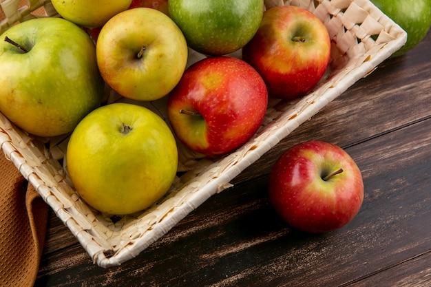 Vue Latérale Des Pommes Vertes Et Rouges Dans Un Panier Sur Une Serviette Marron Sur Un Fond En Bois Photo gratuit