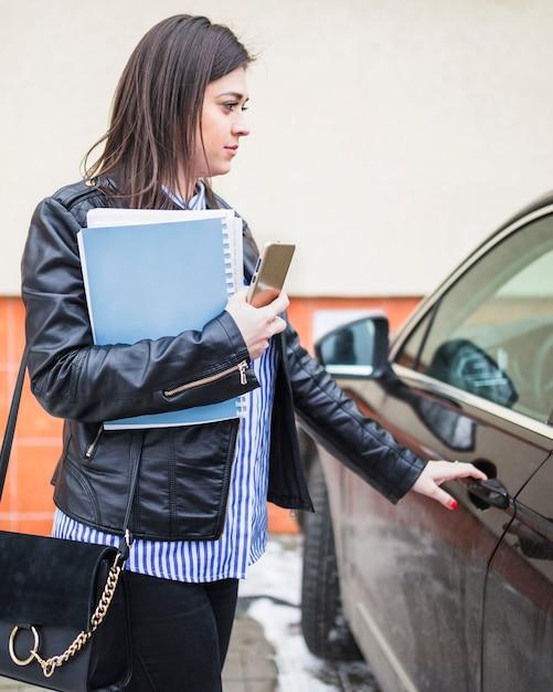 Vue latérale de la porte de la voiture d'ouverture de jeune femme d'affaires Photo gratuit