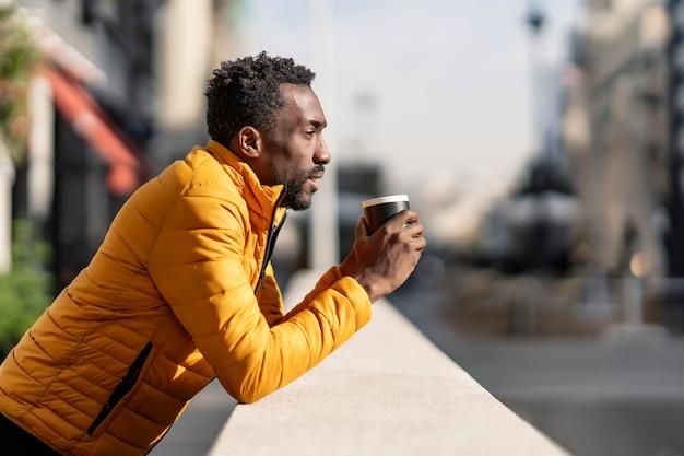 Vue Latérale Portrait D'un Homme Africain Sérieux Appuyé Sur Un Balcon Tenant Une Tasse De Café En Contemplant Des Vues Dans Une Ville Photo Premium