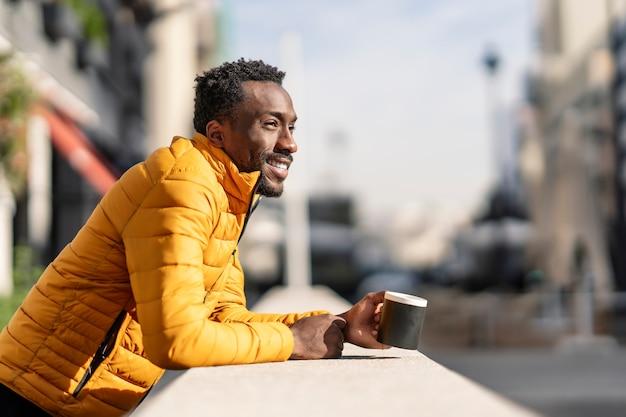 Vue Latérale Portrait D'un Homme Africain Souriant Appuyé Sur Un Balcon Tenant Une Tasse De Café En Contemplant Des Vues Dans Une Ville Photo Premium