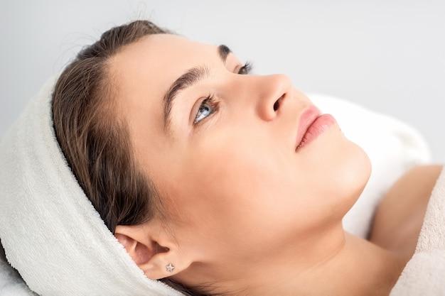 Vue Latérale Portrait De Jeune Femme Pensive Allongée Sur Une Table D'esthéticienne En Attendant La Procédure Cosmétique Dans Un Salon De Beauté Photo Premium