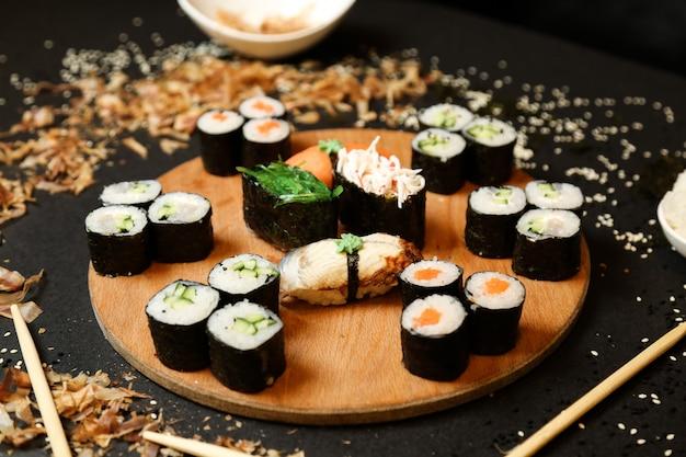 Vue Latérale Des Rouleaux De Kappa Maki Avec Shake Maki Et Sashimi Sushi Avec Des Baguettes Sur Un Support Photo gratuit