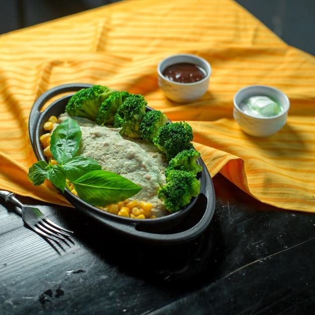 Vue Latérale D'une Salade De Légumes Avec Des Cors Et Des Brocolis Servis Avec Sauce Sur La Table Photo gratuit