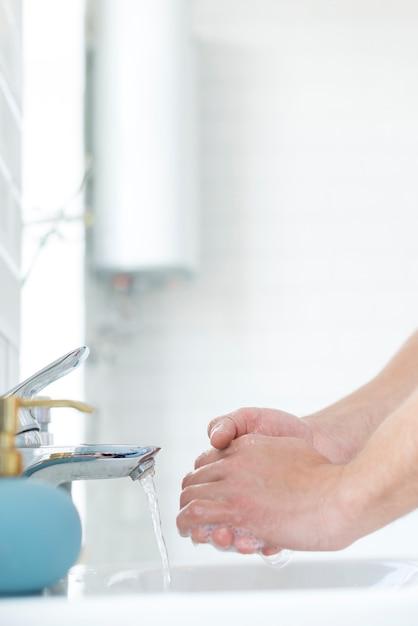Vue Latérale Se Laver Les Mains Dans L'évier Photo gratuit