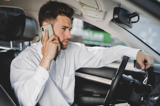 Vue latérale d'un séduisant jeune homme assis dans la voiture, parler sur smartphone Photo gratuit