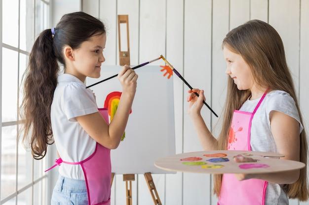 Vue latérale d'un sourire de deux filles touchant leurs pinceaux tout en peignant sur une toile Photo gratuit