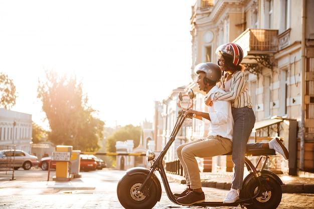 Vue Latérale Sur Toute La Longueur De L'heureux Couple Africain Monte Sur Une Moto Moderne Dans La Rue Photo gratuit