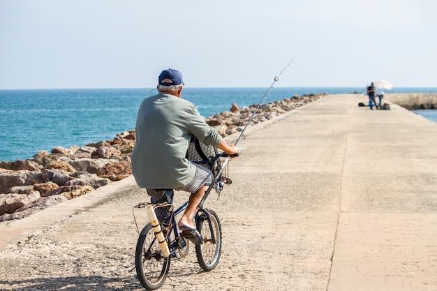 Vue d'un long jet d'eau avec un pêcheur à vélo qui se déplace. Photo Premium