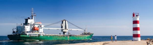 Vue d'un long navire de pêche sortant des marais de ria formosa, situés à faro, en algarve. Photo Premium