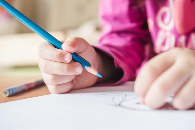 Vue De Mise Au Point Peu Profonde D'un Enfant Portant Un T-shirt Rose Peignant Une Image Avec Le Crayon De Couleur Bleue Photo gratuit