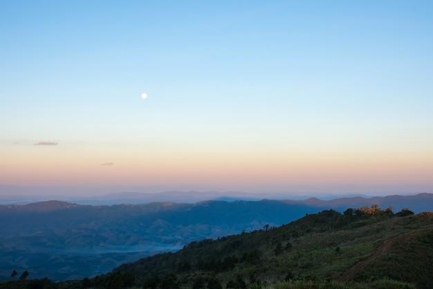 Vue sur la montagne avec la lune dans la matinée. Photo Premium