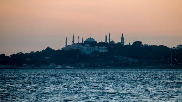 Vue D'une Mosquée Et Beaucoup De Verdure Autour D'elle Le Soir, Le Détroit Du Bosphore Au Premier Plan à Istanbul, Turquie Photo Premium