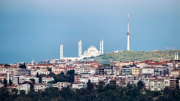 Vue De La Mosquée Camlica Située Sur Une Colline Avec Des Bâtiments Résidentiels Au Premier Plan, Tour Au Sommet De La Colline, Temps Nuageux, Istanbul, Turquie Photo Premium