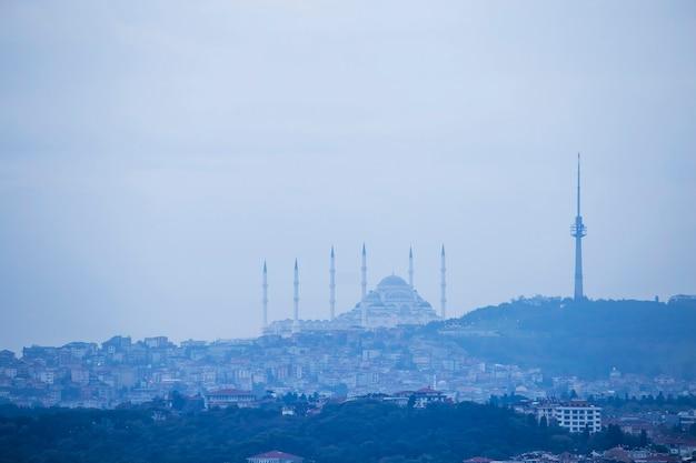 Vue De La Mosquée Camlica Située Sur Une Colline Avec Des Bâtiments Résidentiels Sur La Pente, Tour Au Sommet De La Colline, Temps Nuageux, Istanbul, Turquie Photo Premium