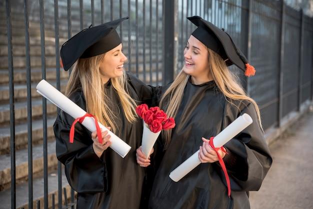 Vue moyenne amis avec bouquet de roses à la remise des diplômes Photo gratuit