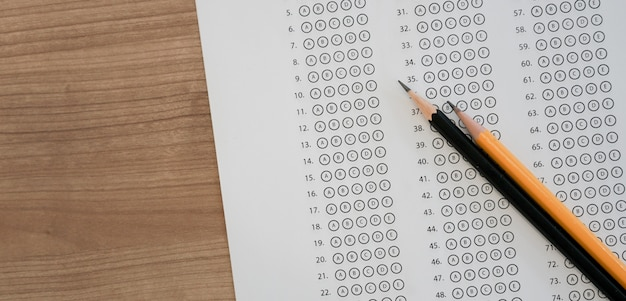 Vue op du crayon noir sur la feuille de réponse à choix multiples avec examen Photo Premium