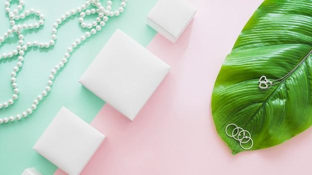 Vue panoramique de boîtes blanches avec des bijoux féminins sur fond de papier Photo gratuit