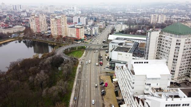 Vue Panoramique De Drone Aérien De Chisinau, Rue Avec Plusieurs Bâtiments Résidentiels Et Commerciaux, Route Avec Des Voitures En Mouvement, Lac Aux Arbres Nus Photo gratuit