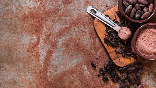 Vue panoramique du chocolat et des fèves de cacao écrasées et bol de poudre Photo gratuit