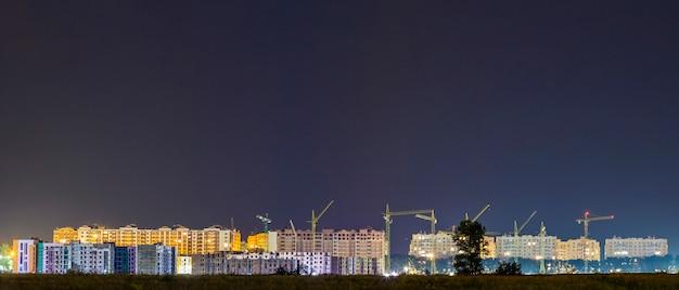Vue panoramique de nuit sur de nombreuses grues sur le chantier de construction d'un nouveau quartier résidentiel moderne Photo Premium