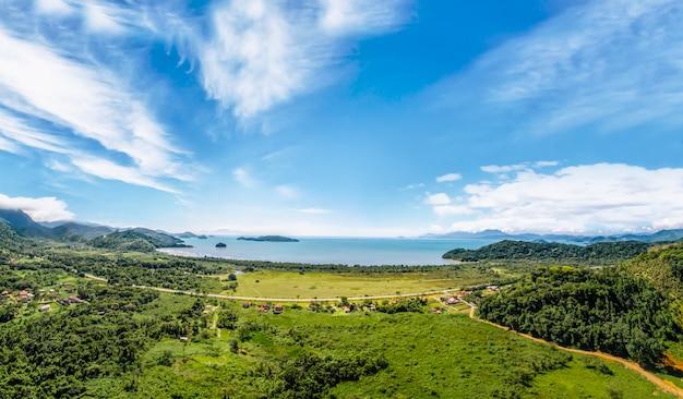 Vue sur le paraty, la plage et l'océan bleu. forêt verte Photo Premium