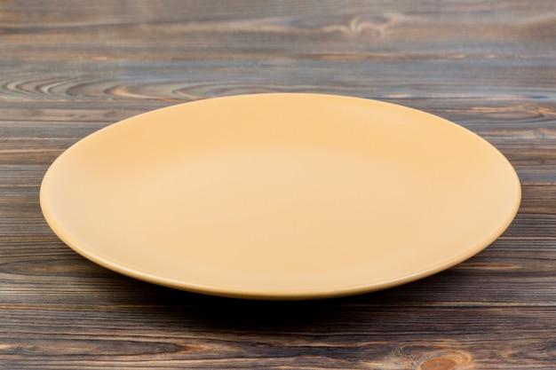 Vue de perspective. assiette mat orange vide sur un fond en bois foncé Photo Premium