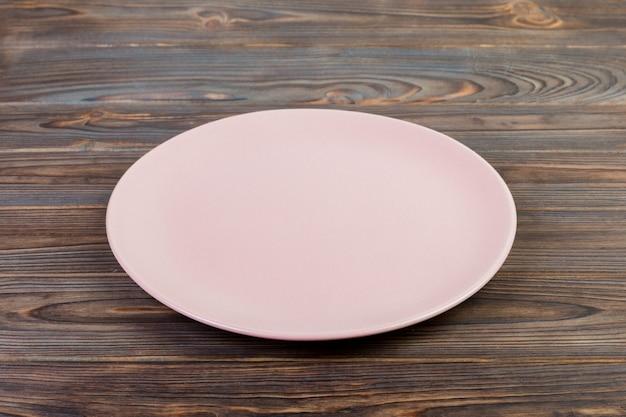 Vue de perspective. plat de matte rose vide pour le dîner sur un fond en bois foncé Photo Premium