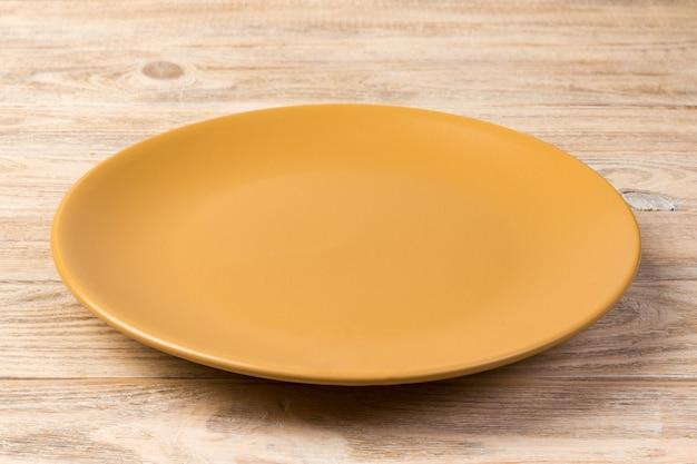 Vue de perspective. plat orange mat vide pour le dîner sur un fond en bois orange Photo Premium