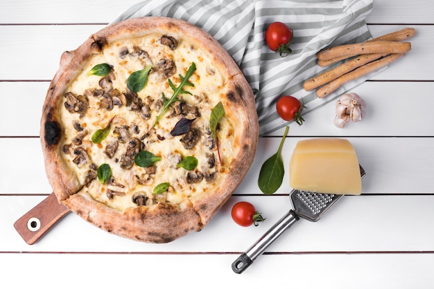 Vue sur la pizza aux champignons maison et bâtons de pain avec des ingrédients sur une planche blanche Photo gratuit
