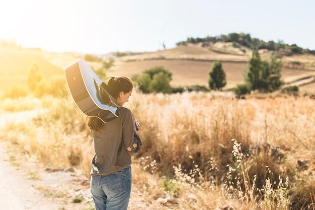 Vue postérieure, de, a, adolescente, tenir guitare, dehors Photo gratuit