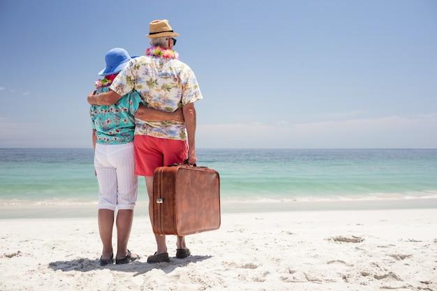 Vue postérieure, de, couples aînés, porter, a, guirlande, et, regarder mer Photo Premium