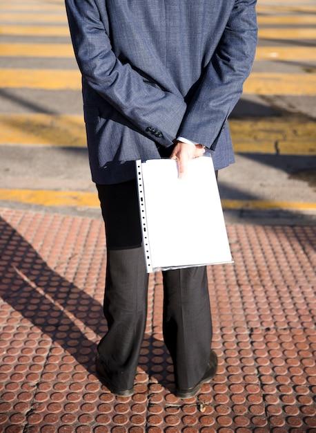 Vue postérieure, de, a, homme, debout, sur, trottoir, tenue, dossier blanc, dans main Photo gratuit