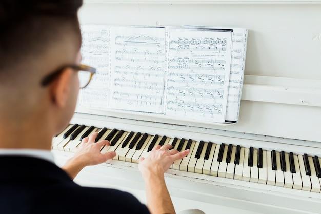Vue postérieure, de, homme, regarder, feuille musicale, jouer piano Photo gratuit