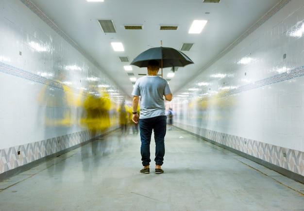 Vue postérieure, de, a, homme, tenue, parapluie, à, floue, gens, longue, exposition, technique Photo gratuit
