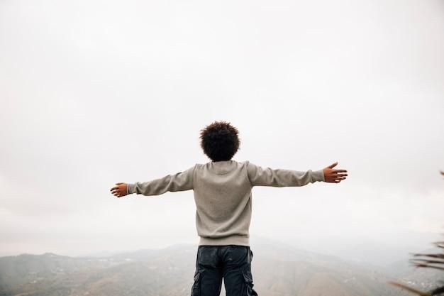 Vue postérieure, de, a, jeune homme africain, debout, au sommet, de, montagne, tendre main Photo gratuit