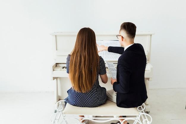 Vue postérieure, de, jeune homme, enseigner, elle, petite amie, piano Photo gratuit