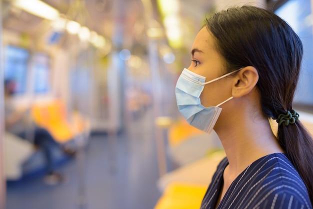 Vue De Profil De Jeune Femme D'affaires Asiatique Avec Masque De Protection Contre L'épidémie De Virus Corona à L'intérieur Du Train Photo Premium