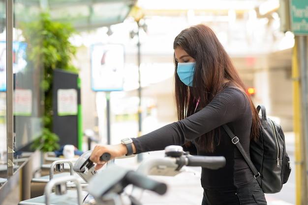 Vue De Profil De Jeune Femme Indienne Avec Masque à Vélo à La Station De Service De Vélos Publics Photo Premium