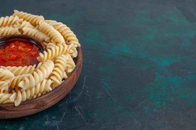 Vue Rapprochée Avant En Forme De Pâtes Italiennes Avec Sauce Tomate Sur Surface Bleu Foncé Photo gratuit