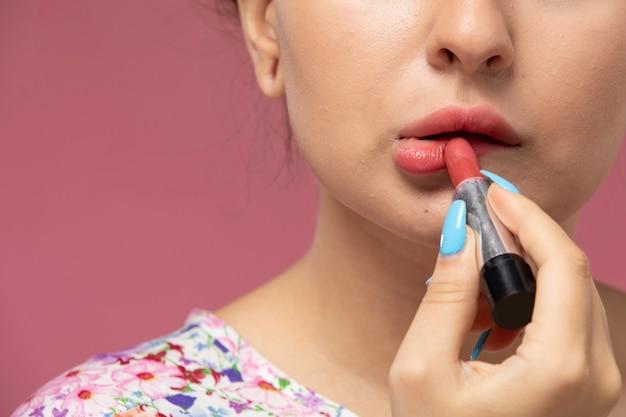 Vue Rapprochée Avant Jeune Femme En Chemise Conçue De Fleurs Faisant Du Maquillage Sur Le Fond Rose Photo gratuit