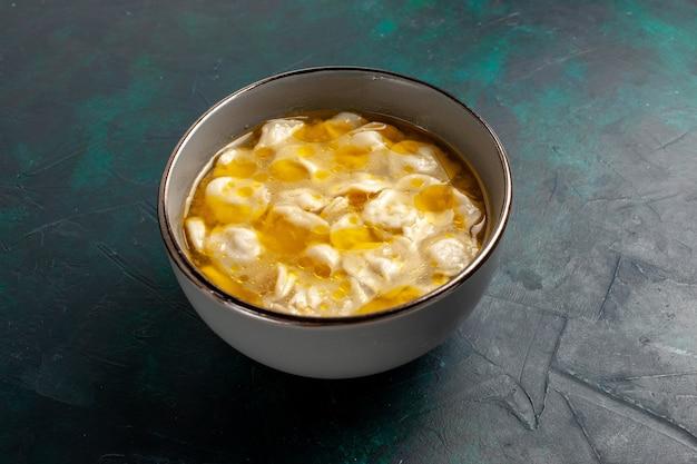 Vue Rapprochée Avant De La Soupe De Pâte Avec De La Viande Hachée à L'intérieur De La Pâte Sur Une Surface Bleu Foncé Photo gratuit