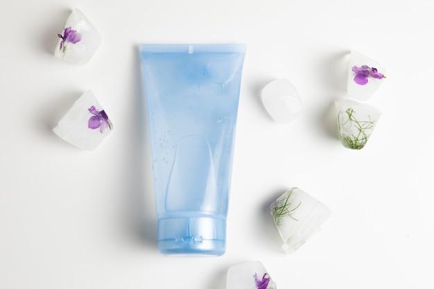 Vue rapprochée de la bouteille bleue et des savons sur fond blanc Photo gratuit