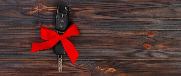 Vue rapprochée des clés de la voiture avec l'arc rouge comme présent sur fond en bois Photo Premium